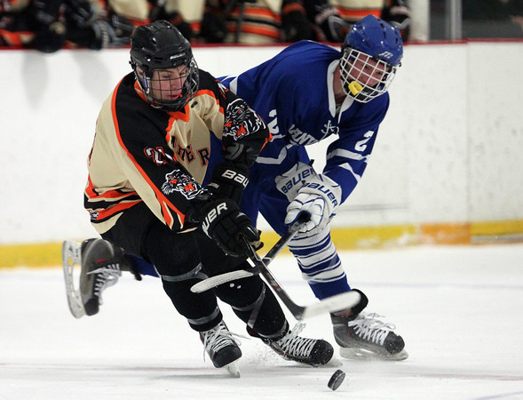 Beverly senior forward Graham Doherty (21) and Danvers junior forward Sean Lundergan (2) get tangled up as they battle for possession of a loose puck during the third period of play on Friday evening in the D2 North Quarter Finals. DAVID LE/Staff Photo 2/28/14