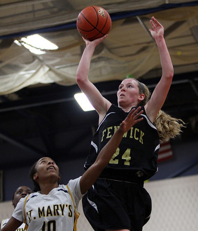 Bishop Fenwick sophomore forward Colleen Corcoran (24) takes a contested jump shot while being defended by St. Mary's senior Sharell Sanders (10) during the second half of play in the D3 North semifinal at Hamilton-Wenham Regional High School on Tuesday evening. DAVID LE/Staff photo
