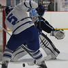 DAVID LE/Staff photo. 2/25/15. Peabody sophomore goalie Aaron McDonnell keeps his eyes on the loose puck in front of him as Danvers senior TJ Deinstadt (5) tries to corral the puck.
