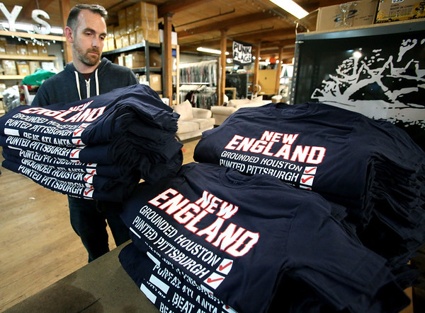 Sully Brand owner, Chris Wrenn, with some of the silkscreened Patriots celebration shirts that his company has been printing and packing.