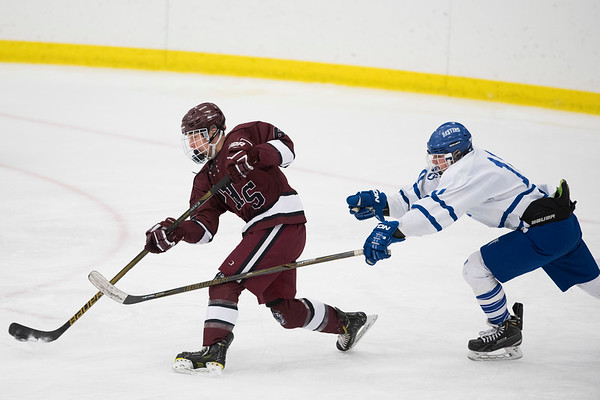 SAM GORESH/Staff photo. Gloucester freshman Harrison Marshall hits the puck as Danvers senior Robert Tibbetts chases him on defense in their game at Salem State University. Danvers won the game 4-0. 2/11/17