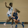 SAM GORESH/Staff photo. Danvers seniorr Nicole White attempts to move the ball as Peabody senior Chinenye Onwuogu attempts to block her on defense in their game at Peabody High School. 2/3/17