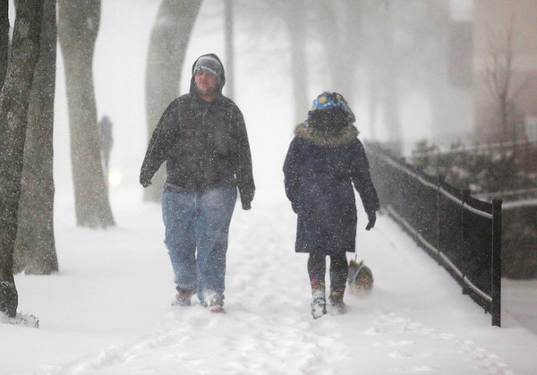 HADLEY GREEN/ Staff photo<br /> A man and a woman pass each other on the sidewalk of Norman Street in Salem during Thursday's snowstorm.