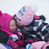 SAM GORESH/Staff photo. Adrianna Giacchino, 10, (right) kisses her cousin Madilyn Smith, 2, (left) after sledding down the hill at Lyons Park. 2/12/17