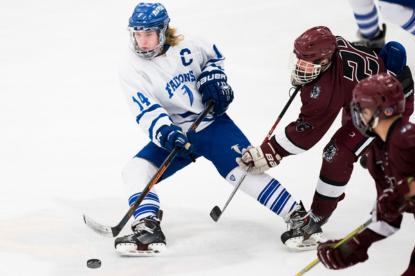 SAM GORESH/Staff photo. Danvers senior Declan Gill prepares to hit the puck as Gloucester senior Liam Lyons fights him on defense in their game at Salem State University. Danvers won the game 4-0. 2/11/17
