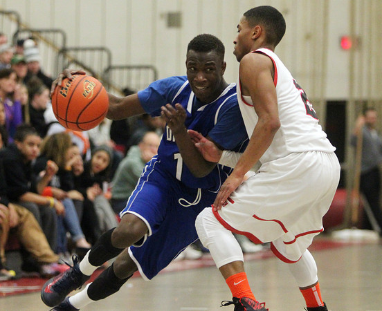 Salem: Danvers sophomore Rashad Francois (1) drives to drive past Salem senior Shaky White (2) during the second half of play. Salem defeated Danvers 41-38 in a closely contested game on Tuesday evening. DAVID LE/Staff Photo 1/14/14