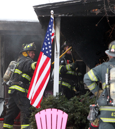 Danvers: A Danvers firefighter breaks down some overhang panels on the roof of 14 Princeton St. in Danvers after a fire broke out in the front room on Tuesday afternoon. DAVID LE/Staff Photo