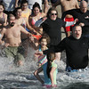 Ken Yuszkus/Staff photo: Salem: Bathers react as they run into the water during the 5th annual Freeze Your Tush Off ocean dip at the Winter Island boat ramp in Salem.