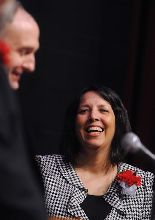 Ken Yuszkus/Staff photo: Salem: Salem Mayor Kim Driscoll laughs at Rev. Dan Riley's humor during his invocation at the Collins Middle School auditorium where the mayor took her oath of office for the third time.