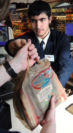 Ken Yuszkus/Staff photo: Marblehead:  Cashier Dave Finestone hands over a plastic bag of groceries at the checkout counter at Crosby's Marketplace in Marblehead.