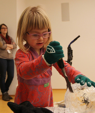 Salem: Julia Street, 4, of Newton, uses a chisel to chip away at a ball of ice during an ice carving demonstration at the Peabody Essex Museum on Saturday afternoon. DAVID LE/Staff Photo