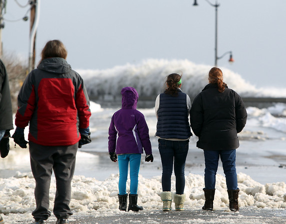 Marblehead: People gathered along Ocean Ave in Marblehead at the edge of Devereaux Beach stare out at the huge waves crashing over the wall of the Causeway on Friday afternoon. DAVID LE/Staff Photo