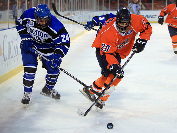 Boston: Salem State freshman forward John Needham (20) tries to corral the puck while being stick checked by UMass Boston defenseman Sam Boyd (24) during the Vikings Frozen Fenway game against UMass Boston on Tuesday afternoon. The Vikings fell to the Beacons 4-2. DAVID LE/Staff Photo