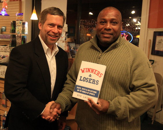 "Marblehead: Sports lawyer Bob Latham, left, shakes hands with his longtime friend Reggie Plaisir, of Marblehead while holding Latham's book, ""Winners & Losers"" at the Spirit of '76 Bookstore in Marblehad on Thursday evening. In addition to a book signing on Thursday, Latham will be speaking at a fundraiser for Northeastern Sports Fund and Skillz Academy Friday evening starting at 6:30pm at The Landing in Marblehead. DAVID LE/Staff Photo"