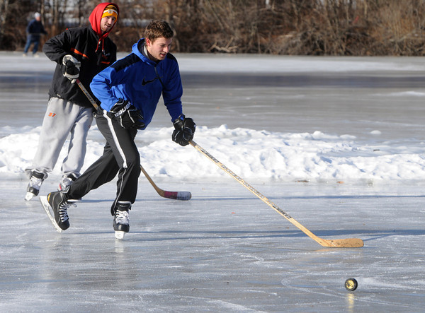 Ken Yuszkus/Staff photo: Beverly: Max Gansenberg, left, and Matthew Bourque pass a puck around while ice skating on Kellehers Pond in Beverly.