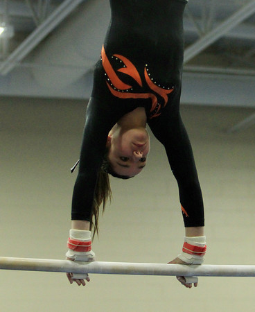 Marblehead: Beverly gymnast Kara McGillvay flips upside down on the uneven bars during her routine against Marblehead in an NEC gymnastics clash at the Lynch/van Otterloo YMCA on Wednesday evening. DAVID LE/Staff Photo 1/8/14