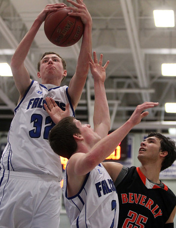 Danvers: Danvers junior Peter Merry (32) grabs a rebound over teammate Mark McCarthy (3) and Beverly senior Jon Berchoff (25) during an NEC clash between the Panthers and Falcons. Danvers rallied from a third quarter deficit to defeat Beverly 65-52 on Friday evening at Danvers High School. DAVID LE/Staff Photo 1/10/14