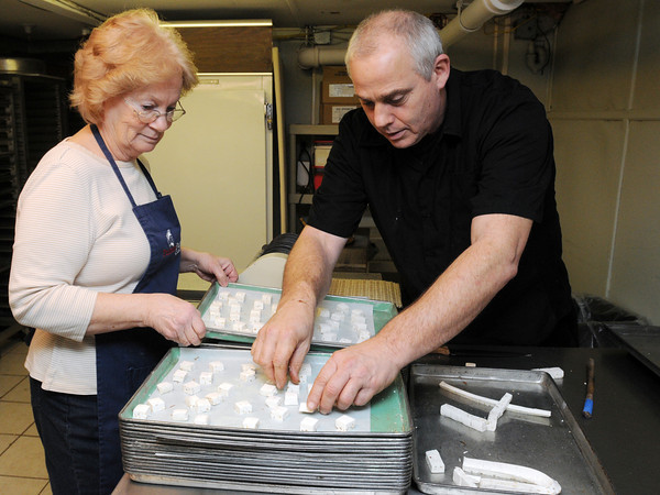 Ken Yuszkus/Staff photo:  Nancy Comeau and Mick Gardner spread out the just cut honey nougat candy on trays at Putnam Pantry.