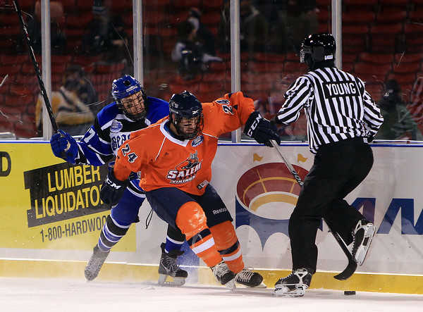 Boston: Salem State freshman Brandon Platt (24) fends off UMass Boston sophomore Derek Colucci (17) and carries the puck up the boards during the Vikings Frozen Fenway game against UMass Boston on Tuesday afternoon. The Vikings fell to the Beacons 4-2. DAVID LE/Staff Photo