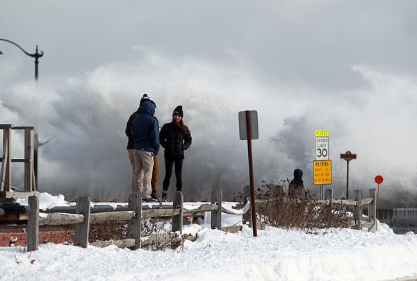 Marblehead: Curious onlookers stood atop a couple docks as high waves crashed over the causeway wall behind them on Friday afternoon as high tide hit Devereaux Beach in Marblehead. DAVID LE/Staff Photo
