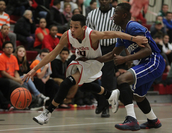 Salem: Salem junior Michael Sanchez (10) drives past Danvers sophomore Rashad Francois (1) and to the hoop during the first half of play. Salem defeated Danvers 41-38 in a closely contested game on Tuesday evening. DAVID LE/Staff Photo 1/14/14