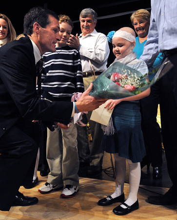 Ken Yuszkus/Staff photo: Beverly: Beverly Mayor Michael Cahill gives a bouquet of flowers to Riley Fessenden, 6, on stage during the Beverly inaugural held at Beverly High School. He had just presented a large key to the city to her.