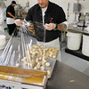 Ken Yuszkus/Staff photo: Salem: Ken's Kickin Chicken worker Darrell Kain covers stuffed mushrooms with cellophane.