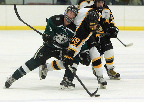 Peabody: Austin Prep junior Ryan McDonough (13) puts his shoulder into Bishop Fenwick's Chris Napolitano (19) as he carries the puck across the Cougars blue line on Saturday evening. The Crusaders fell 11-0 to the Cougars in Catholic Central League action at the McVann-O'Keefe Rink. DAVID LE/Staff Photo