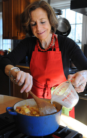Ken Yuszkus/Staff photo: Salem:  Cook and author Nina Simonds pours coconut milk into the pot as part of the recipe for curried tofu with vegetables.