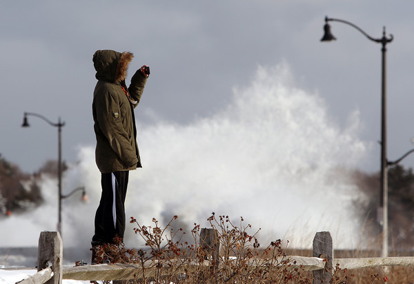 Marblehead: Mike Colucci, of Marblehead, takes a video of the flooding at Devereaux Beach as waves crash over the wall on the causeway behind him on Friday afternoon. DAVID LE/Staff Photo