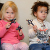 Ken Yuszkus/Staff photo: Beverly: Naomi Butterworth, 2 1/2, left, and Jayden Beal, 2, ring bells to accompany the singing of a song during story hour for toddlers at the Beverly Public Library on Tuesday morning.
