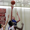 Salem: Danvers junior forward Peter Merry (32) takes a floater over Salem senior David Kazadi (5) during the second half of play on Tuesday evening. Salem defeated Danvers 41-38 in a closely contested game on Tuesday evening. DAVID LE/Staff Photo 1/14/14
