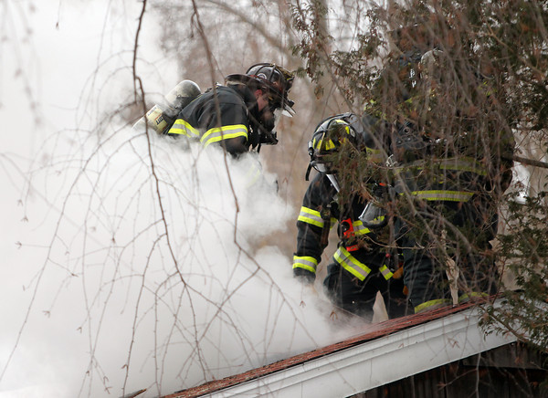 Danvers: Three Danvers firefighters punch a hole in the roof of 14 Princeton St. in Danvers after a fire broke out in the front room on Tuesday afternoon. DAVID LE/Staff Photo