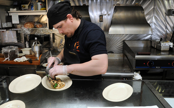 Ken Yuszkus/Staff photo: Salem:  Cook Shane Worthington places one of the breakfast orders on a plate at The Salem Diner on Wednesday morning.