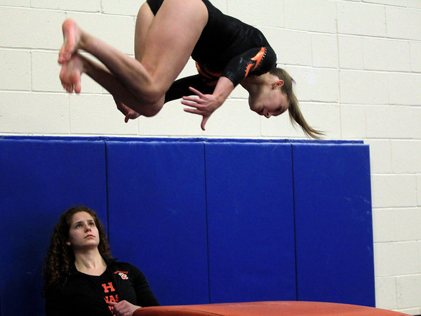 Marblehead: Beverly gymnast Chloe Cavanaugh, under the watchful eye of Panthers head coach Lauryn Ginsburg, explodes off the vault during a meeting between the Magicians and Panthers in an NEC gymnastics clash at the Lynch/van Otterloo YMCA on Wednesday evening. DAVID LE/Staff Photo 1/8/14