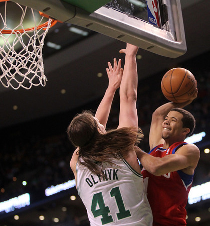 Boston: Philadelphia 76ers rookie guard Michael Carter-Williams (1) goes up strong to the hoop and tries to fend off the block attempt from Boston Celtics rookie forward Kelly Olynyk (41) during the fourth quarter of play on Wednesday evening at the TD Garden. DAVID LE/Staff Photo 1/29/14