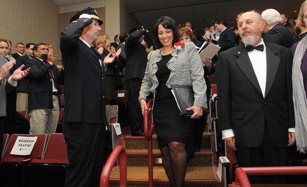Ken Yuszkus/Staff photo: Salem: Salem Mayor Kim Driscoll enters the Collins Middle School auditorium to take her oath of office for the third time at the start of the Salem inaugural. Salem Police Chief Paul Tucker, left, salutes as she passes by.
