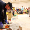 Salem: Lars Miller, of Brilliant Ice Sculptures, uses a chainsaw to cut a block of ice in half during a demonstration at the Peabody Essex Museum on Saturday afternoon. DAVID LE/Staff Photo