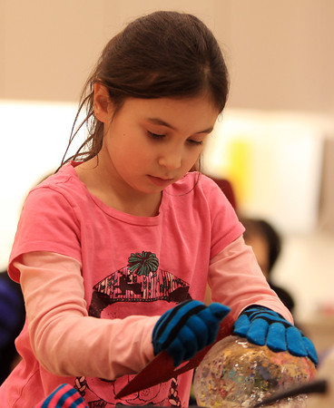 Salem: Rebecca Vaynshteyn, 7, of Salem, uses a piece of sandpaper to form a ball of ice during an ice carving demonstration put on by Brilliant Ice Sculptures at the Peabody Essex Museum on Saturday afternoon. DAVID LE/Staff Photo