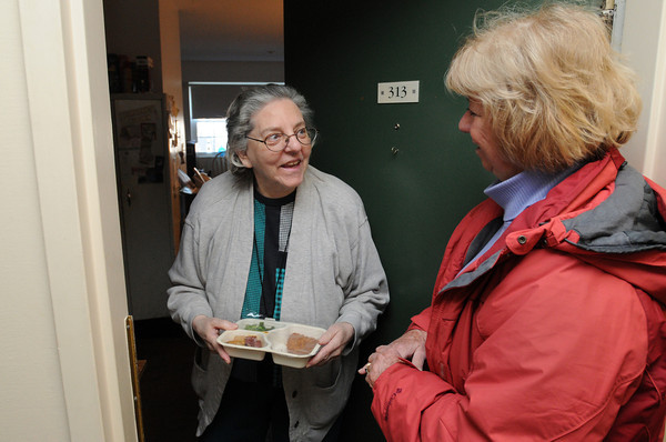 Ken Yuszkus/Staff photo: Peabody: Meals On Wheels driver Christine Phillips, right, delivers a meal to Peabody resident Barbara Klayman.