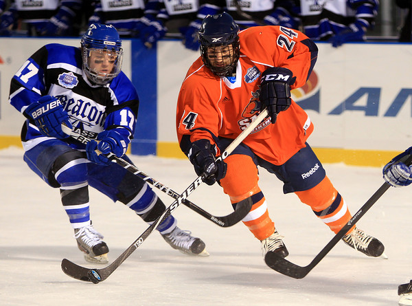Boston: Salem State freshman forward Brandon Platt (24) manages to keep ahold of the puck while being stick checked by UMass Boston sophomore Derek Colucci (17) during the Vikings Frozen Fenway game against UMass Boston on Tuesday afternoon. The Vikings fell to the Beacons 4-2. DAVID LE/Staff Photo