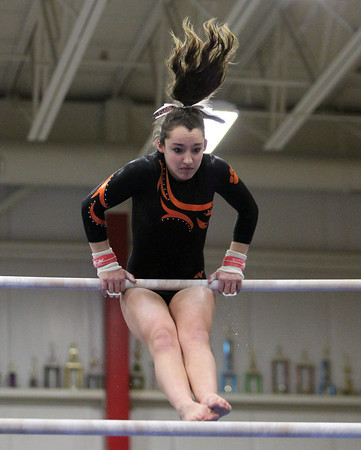 Beverly: Beverly gymnast Kara MacGilvary flips over the bar while performing her routine against Masco at the Sterling Center YMCA on Friday evening. DAVID LE/Staff Photo 1/31/14
