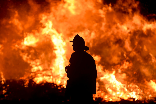 Lieutenant Scott Hebert of the Salem Fire Department is silhouetted by Salem's 14th annual Christmas tree bonfire at Dead Horse Beach. 1/6/17