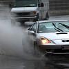 Cars drive through the rain puddles on Bridge Street in Salem