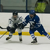 SAM GORESH/Staff photo. Peabody senior Tim January reaches for the puck as Danvers freshman Shane Cassidy attempts to stop him on defense in their game at McVann-O'Keefe Rink. 1/10/17