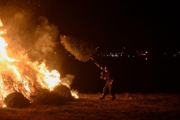 Lieutenant Scott Hebert of the Salem Fire Department throws a Christmas tree on the bonfire during Salem's 14th annual Christmas tree bonfire at Dead Horse Beach. 1/6/17