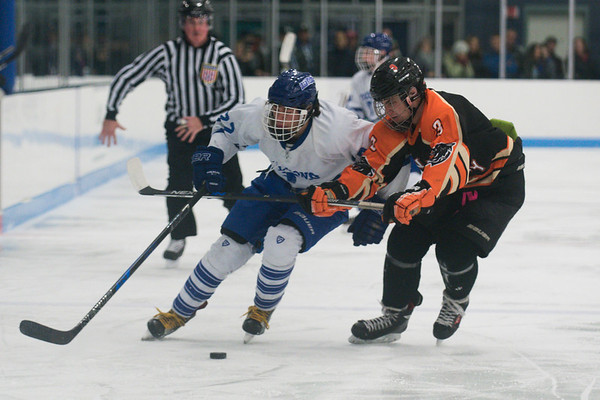 SAM GORESH/Staff photo. Beverly senior Terran Mazzagliz attempts to stop Danvers junior Thomas Mento from taking control of the puck in their game at Bourque Arena. 1/6/17