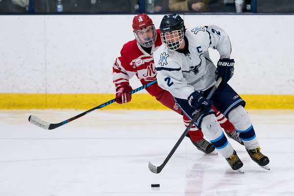 SAM GORESH/Staff photo. Peabody senior Tim January takes control of the puck as  Masconomet junior Dylan Campbell races to try to stop him on defense in the inaugural 'Can Do' Classic. The game ended in a 3-3 tie. 1/2/17