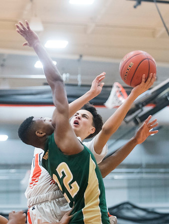 Beverly sophomore Tuscany Abreu attempts a basket as Lynn Classical junior Ishmael Johnson attempts to stop him on defense in their game at Beverly High School. Lynn Classical won the game 68-65. 1/27/17