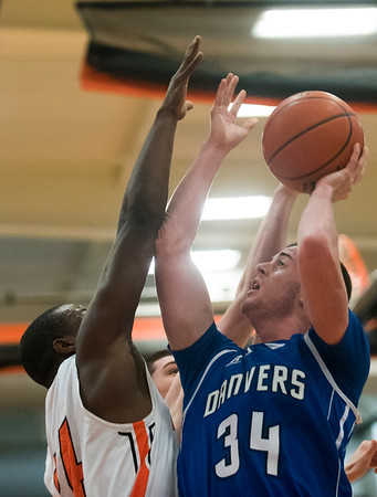 Danvers senior Kieran Moriarty goes up for a basket as Beverly senior Hugh Calice attempts to block him on defense in their game at Beverly High School. 1/3/17